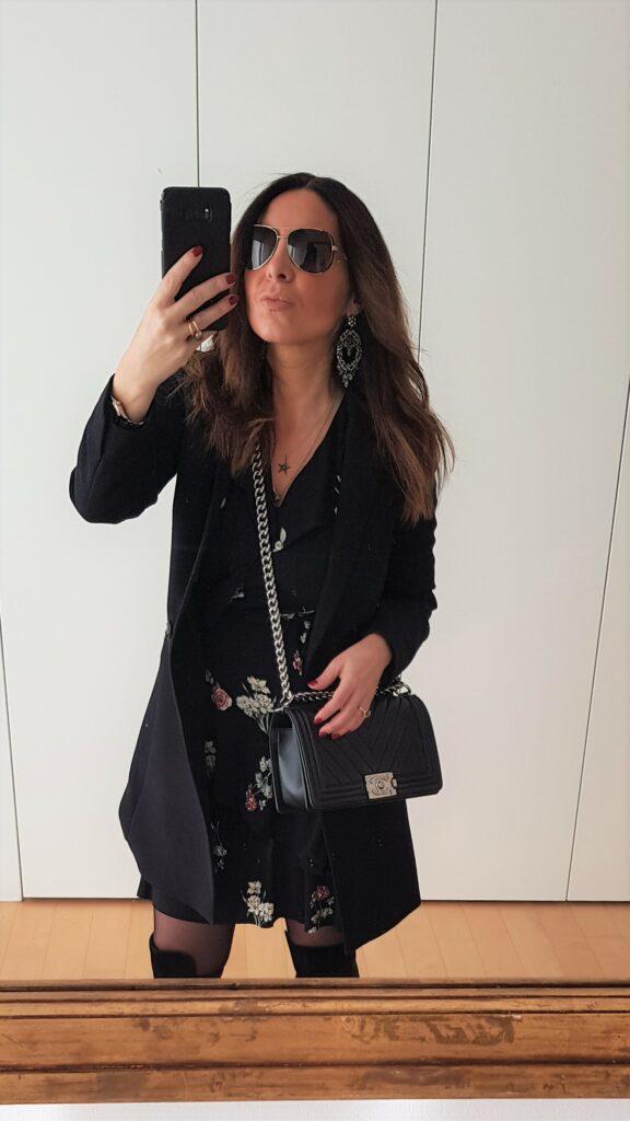 Outfit serale per la primavera con Chanel Boy e vestito a fiori. Cappotto leggero nero, abito incrociato Liu Jo, Chanel Boy Bag, stivali cuissardes.