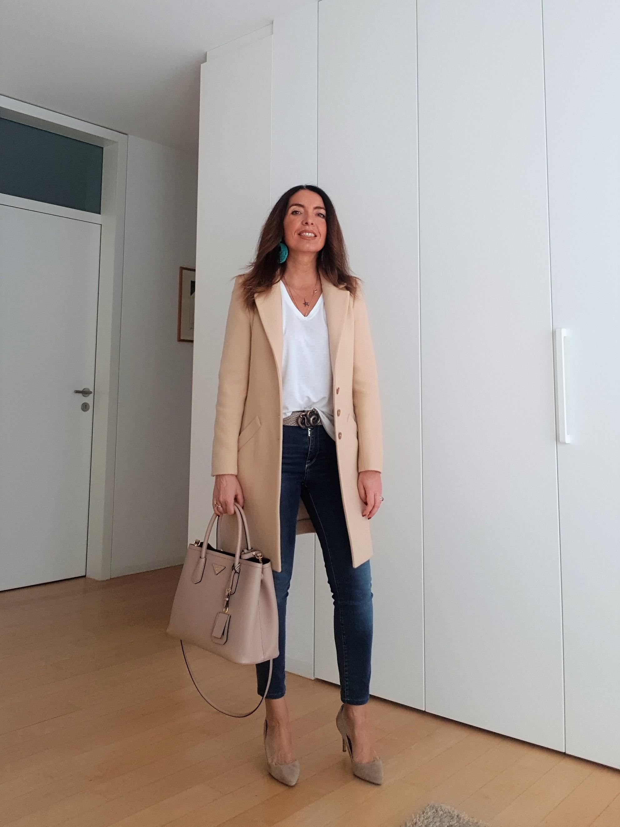 Outfit primaverile che abbina jeans e cappotto beige. Orecchini turchesi e borsa Prada Double.