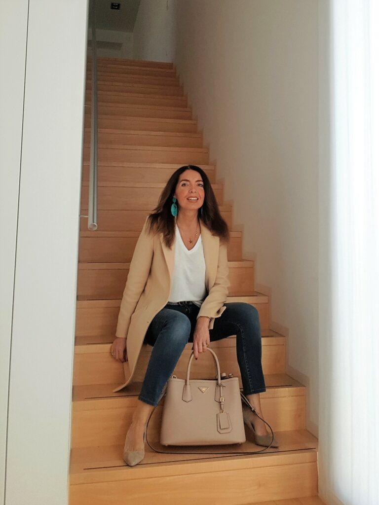 Outfit da seduta: jeans, cappotto cammello e borsa beige. Orecchini turchesi