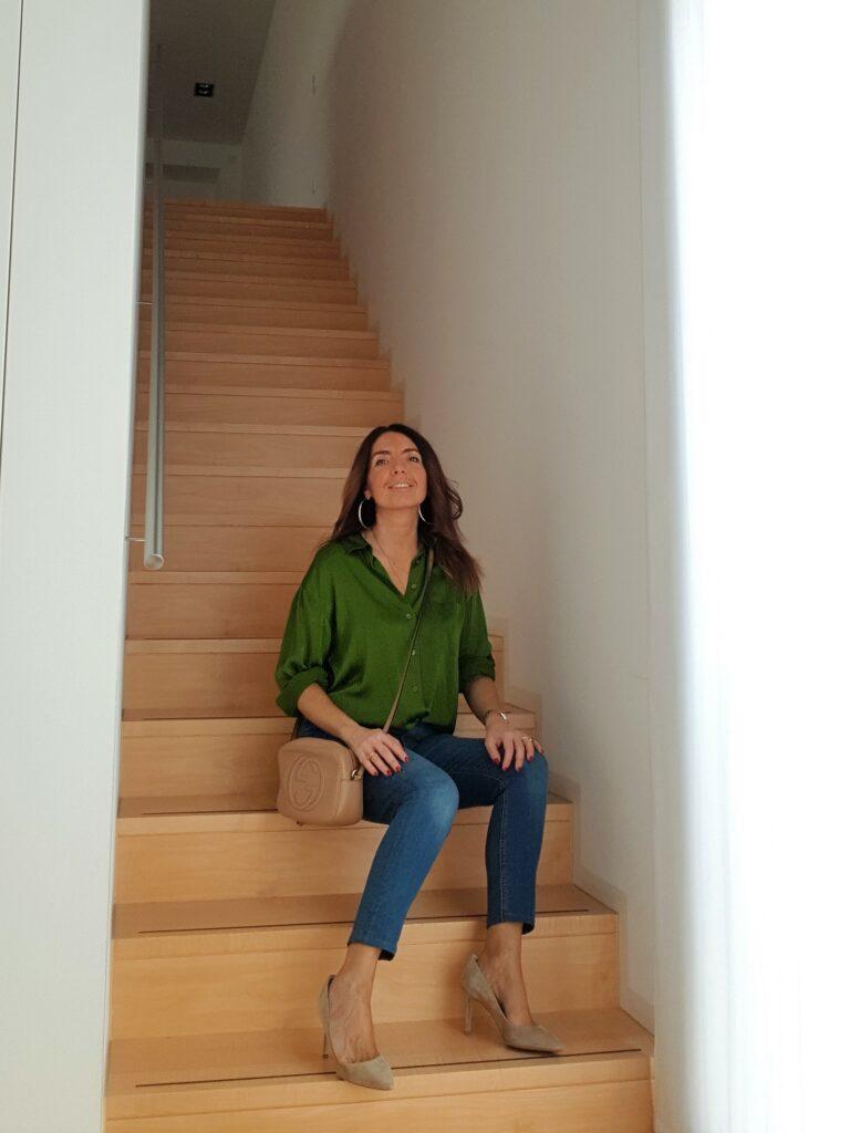 Abbinamento jeans e blusa verde da seduta con borsa Gucci