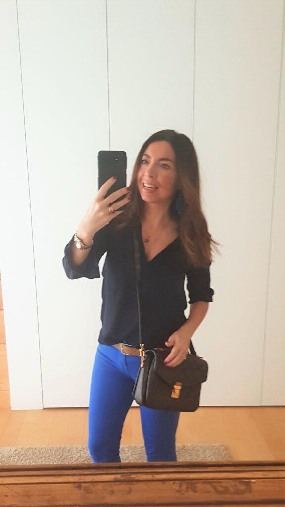 Pochette Métis outfit: pantaloni blu cobalto e blusa blu scura. Giacca in pelle blu.