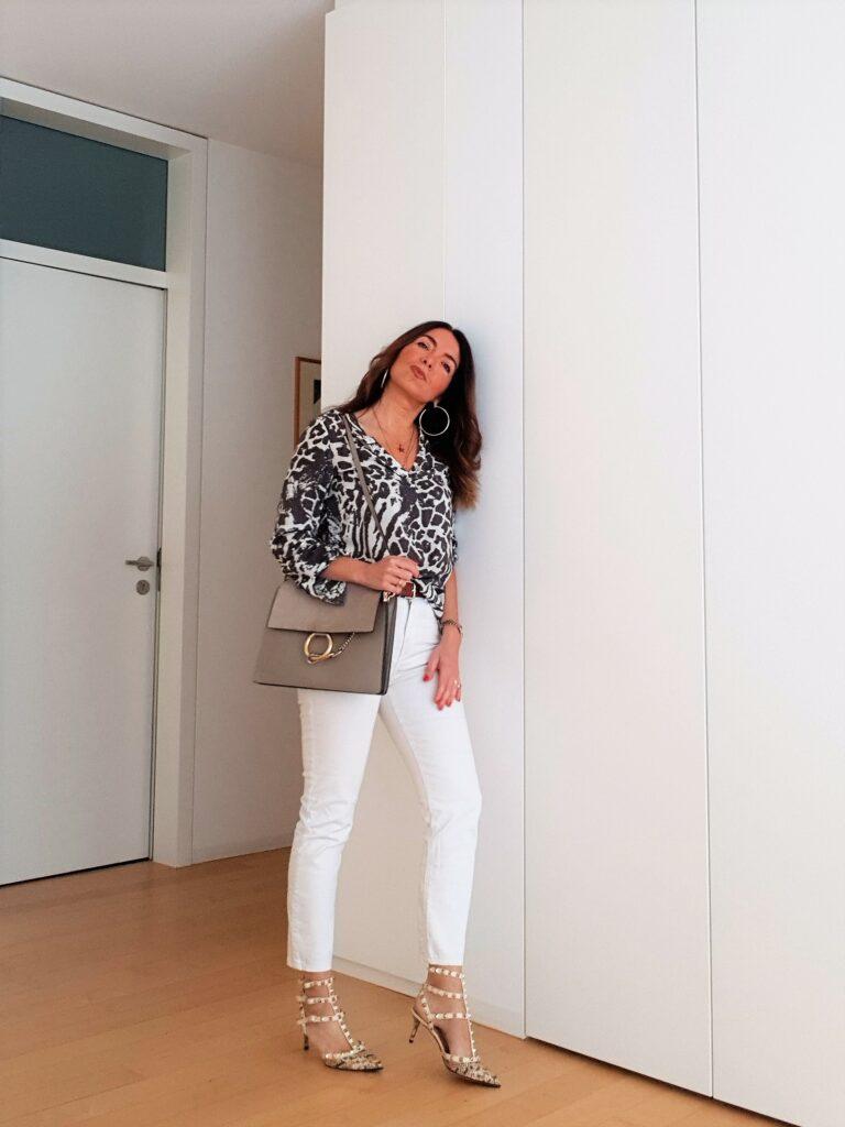 Oufit primaverile con jeans bianchi, blusa fantasia e borsa Chloé Faye e Valentino Rockstud